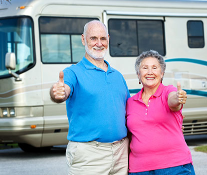 older couple in front of recreational vehicle